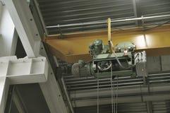 Ciérrese para arriba de una grúa de arriba de la fábrica interior en un haz amarillo imágenes de archivo libres de regalías