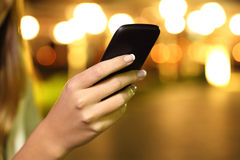 Ciérrese para arriba de una mano de la mujer usando un teléfono elegante en la noche Fotografía de archivo libre de regalías