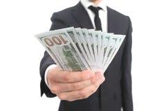 Ciérrese para arriba de una mano del hombre de negocios que sostiene el dinero Foto de archivo