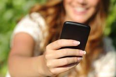 Ciérrese para arriba de una mano feliz de la mujer usando un teléfono elegante Fotografía de archivo libre de regalías