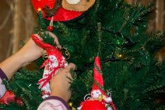 Ciérrese para arriba de una mano que viste el árbol de navidad con DEC hecho en casa Foto de archivo libre de regalías
