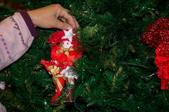 Ciérrese para arriba de una mano que viste el árbol de navidad con DEC hecho en casa Fotos de archivo