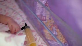 Ciérrese para arriba de una mano recién nacida en una caja especial para los bebés prematuros, al lado de una jeringuilla Unidad  almacen de video