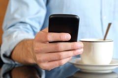 Ciérrese para arriba de una mano usando un teléfono elegante en el desayuno Imágenes de archivo libres de regalías