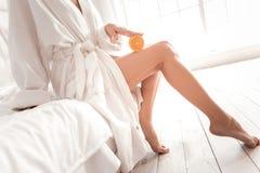 Ciérrese para arriba de una mitad anaranjada que es presionada a la pierna Imagen de archivo libre de regalías