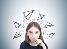 Ciérrese para arriba de una muchacha adolescente pensativa, aviones de papel Foto de archivo