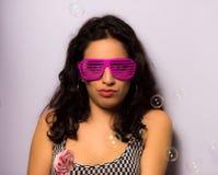 Ciérrese para arriba de una muchacha hermosa con las burbujas de jabón del maquillaje que soplan profesional alrededor de ella Fotos de archivo libres de regalías