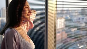 Ciérrese para arriba de una muchacha que mira hacia fuera la ventana metrajes