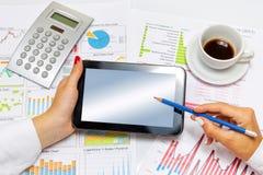 Ciérrese para arriba de una mujer de negocios que hace la presentación en la tableta, en el escritorio de oficina Foto de archivo libre de regalías