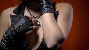 Ciérrese para arriba de una mujer del eje de balancín con los guantes de cuero y las porciones de pulseras metrajes