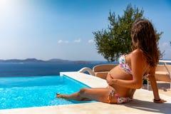 Ciérrese para arriba de una mujer embarazada que se relaja en la piscina imagenes de archivo