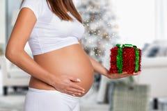 Ciérrese para arriba de una mujer embarazada que sostiene un regalo de la Navidad imagenes de archivo