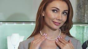 Ciérrese para arriba de una mujer feliz magnífica que intenta en un collar de la perla almacen de metraje de vídeo
