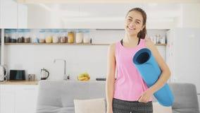 Ciérrese para arriba de una mujer hermosa joven vestida en activar azul o de una estera de la aptitud después de trabajar en casa