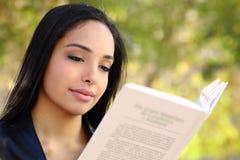 Ciérrese para arriba de una mujer hermosa que lee un libro en un parque Imagen de archivo libre de regalías