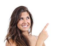 Ciérrese para arriba de una mujer hermosa que señala y que mira arriba Imagen de archivo libre de regalías