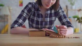 Ciérrese para arriba de una mujer joven con un rosario en sus manos que lee la biblia almacen de metraje de vídeo