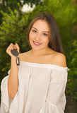 Ciérrese para arriba de una mujer joven hermosa sonriente que lleva a cabo sus llaves y que presenta para la cámara en fondo borr Fotos de archivo libres de regalías