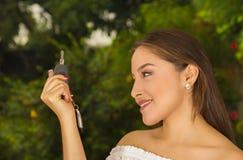 Ciérrese para arriba de una mujer joven hermosa sonriente que lleva a cabo sus llaves y que presenta para la cámara en fondo borr Imagenes de archivo