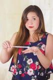 Ciérrese para arriba de una mujer joven sorprendida que lleva a cabo en sus manos un objeto médico y la crema utilizó para la med Foto de archivo libre de regalías