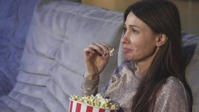 Ciérrese para arriba de una mujer madura que come las palomitas que sonríen en el cine almacen de video