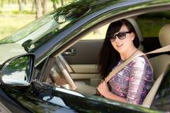 Ciérrese para arriba de una mujer morena atractiva en un coche imagen de archivo