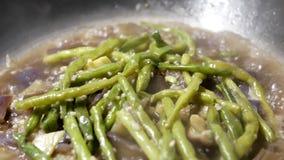 Ciérrese para arriba de una mujer que cocina el pote caliente de la haba verde de la berenjena y del ajo almacen de video