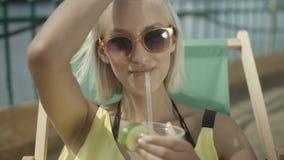 Ciérrese para arriba de una mujer que goza de un cóctel tropical del mojito adornado con la fruta fresca almacen de video