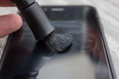 Ciérrese para arriba de una mujer que limpia el teléfono elegante móvil con la tela en el fondo oscuro, texto en blanco, Foto de archivo libre de regalías