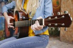 Ciérrese para arriba de una mujer que toca una guitarra acústica Fotos de archivo