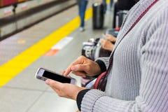 Ciérrese para arriba de una mujer que usa el teléfono elegante móvil Foto de archivo libre de regalías