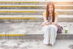 Ciérrese para arriba de una mujer que usa el teléfono elegante móvil Foto de archivo