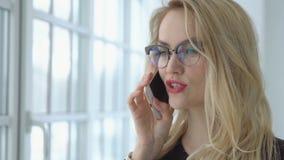 Ciérrese para arriba de una mujer rubia que habla en el teléfono por la ventana almacen de metraje de vídeo