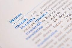 Ciérrese para arriba de una palabra del TRADUCIR en un diccionario foto de archivo