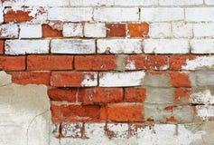 Ciérrese para arriba de una pared de ladrillo necesitando la reparación con agrietar y la peladura de la pintura Imagenes de archivo
