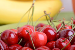 Ciérrese para arriba de una pila fresca de fruta que consiste en cerezas y plátanos imagenes de archivo
