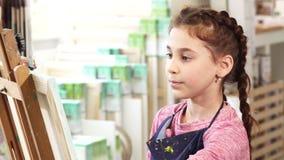 Ciérrese para arriba de una pintura linda de la niña en el caballete en la escuela