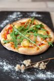 Ciérrese para arriba de una pizza con arugula en una guarnición de la pizarra con la harina imagen de archivo