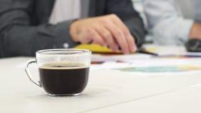 Ciérrese para arriba de una taza de café en los empresarios de la tabla que trabajan en el fondo fotos de archivo