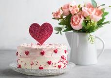 Ciérrese para arriba de una torta adornada con los pequeños corazones con el primero de la torta del corazón, contra un fondo gri foto de archivo libre de regalías