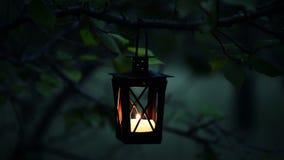 Ciérrese para arriba de una vela linda en luces de la linterna de la vela en el crepúsculo