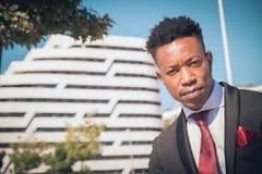 Ciérrese para arriba de uno joven y del hombre de negocios negro atractivo que mira la cámara delante de un edificio moderno en l imagenes de archivo