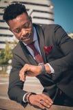 Ciérrese para arriba de uno joven y del hombre de negocios negro atractivo que pasa a través de un paso de peatones y que habla p foto de archivo libre de regalías