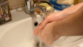 Ciérrese para arriba de varón caucásico, lavando las manos con el jabón líquido, funcionamiento del agua, fregadero del cuarto de almacen de metraje de vídeo