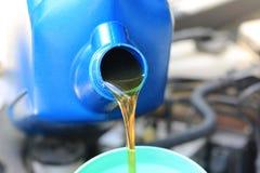 Ciérrese para arriba de verter el aceite fresco al motor de coche en servicio de reparación auto, aceite del cambio fotografía de archivo libre de regalías