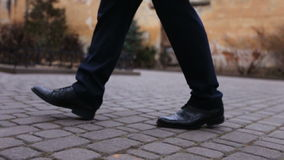 Ciérrese para arriba de zapatos y de pantalones de un novio que camina en la calle metrajes