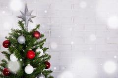 Ciérrese para arriba del árbol de navidad sobre la pared de ladrillo blanca con nieve fotos de archivo