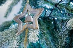 Ciérrese para arriba del árbol Nevado de la Navidad con una estrella de madera y una Bell D Foto de archivo