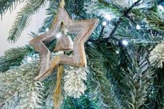 Ciérrese para arriba del árbol Nevado de la Navidad con una estrella de madera y una Bell D Fotografía de archivo libre de regalías