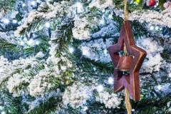 Ciérrese para arriba del árbol Nevado de la Navidad con una estrella de madera y una Bell D imagen de archivo libre de regalías